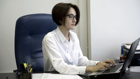 Young and beautiful businesswoman with short, dark hair in white shirt is tired from work in the office. Young office stock photo
