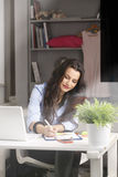 Young beautiful businesswoman sitting at desk and working at hom Stock Images