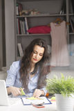 Young beautiful businesswoman sitting at desk and working at hom Royalty Free Stock Photos