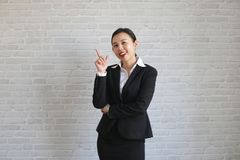 Young beautiful businesswoman smiling looking at camera pointing finger in side over white background royalty free stock photos