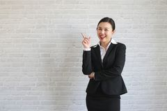Young beautiful businesswoman smiling looking at camera pointing finger in side over white background stock photography