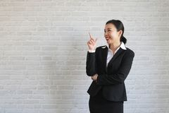 Young beautiful businesswoman smiling looking at camera pointing finger in side over white background stock photos