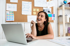 Young beautiful businesswoman smiling, sitting at workplace typing on laptop. Office background. Royalty Free Stock Image