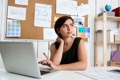 Young beautiful businesswoman thinking, sitting at workplace with laptop. Office background. Stock Photos