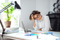 Young beautiful businesswoman thinking at workplace in office. Young beautiful tired businesswoman thinking at workplace in office Stock Photography