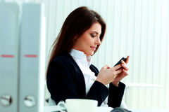 Young beautiful businesswoman typing on her smartphone Stock Images