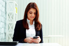 Young beautiful businesswoman typing on her smartphone Royalty Free Stock Photo