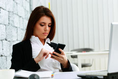 Young beautiful businesswoman typing on her smartphone stock image