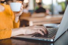 young beautiful businesswomen wearing a yellow sweater enjoying coffee during work on portable laptop computer. stock photos
