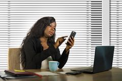 Young beautiful and busy black African American businesswoman using mobile phone working on desk with laptop computer at company stock photo