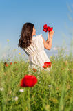 Young beautiful calm girl dreaming on a poppy field, summer outdoor. Royalty Free Stock Photo