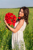 Young beautiful calm girl dreaming on a poppy field, summer outdoor Stock Photo