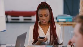 Young beautiful casual African American corporate employee distracted, using smartphone at team meeting office table.