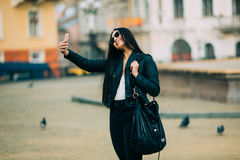 Young beautiful casual girl takes a selfie on her cell phone Royalty Free Stock Images