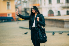 Young beautiful casual girl takes a selfie on her cell phone with sunglasses Stock Photo