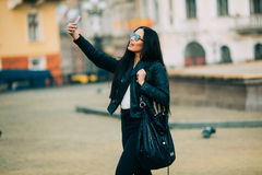 Young beautiful casual girl takes a selfie on her cell phone with sunglasses Royalty Free Stock Images