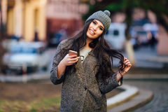 Young beautiful casual girl texting on her cell phone  on  spring city street Royalty Free Stock Photos