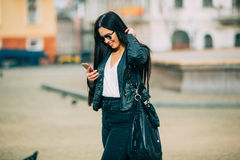 Young beautiful casual woman texting/calling on her cell phone. With sunglasses in jacket an black bag smile to camera on  spring city street. Spring outfit Stock Photo