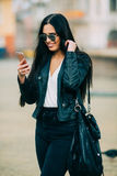 Young beautiful casual woman texting/calling on her cell phone Royalty Free Stock Images