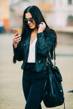 Young beautiful casual woman texting/calling on her cell phone Stock Photos