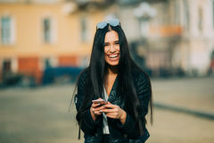 Young beautiful casual woman texting/calling on her cell phone Stock Photography