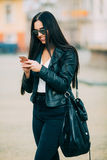 Young beautiful casual woman texting/calling on her cell phone. With sunglasses in jacket an black bag smile to camera on  spring city street. Spring outfit Royalty Free Stock Image