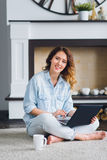 Young beautiful casual woman working on a laptop sitting on the floor in the house. Stock Images