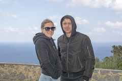 Young beautiful casually dressed couple stand high up watching out to sea. Young beautiful casually dressed couple, with sunglasses and hood jackets, stand high royalty free stock photography