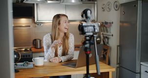 Young beautiful Caucasian blonde woman beauty blogger laughing while recording social media vlog at home slow motion. Happy smiling female vlogger making a new stock video footage