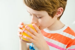 Young beautiful caucasian boy drinking orange juice from glass Royalty Free Stock Photos