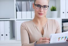 Young beautiful Caucasian businesswoman in glasses locing in camera while working on notebook computer and business. Businesswoman working on notebook computer royalty free stock photo