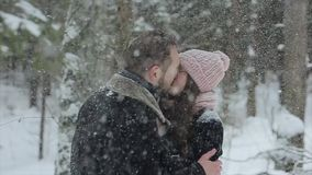 Young beautiful caucasian couple kissing under a snow in a winter forest. Fashionable millennials having fun toghether stock video footage