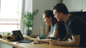 Young beautiful caucasian couple sitting in modern kitchen at table in front of laptop skyping with two girls, they are. Showing something in a big bag, smiling stock video