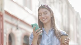 Young beautiful caucasian girl with brown hair and headband on it wearing striped shirt using her smartphone. Woman stock footage