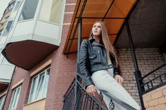 Young beautiful caucasian girl posing in a black leather jacket on a brick wall background. royalty free stock photo