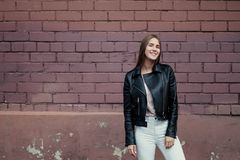 Young beautiful caucasian girl posing in a black leather jacket on a brick wall background. stock images