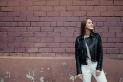Young beautiful caucasian girl posing in a black leather jacket on a brick wall background. royalty free stock image