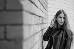 Young beautiful caucasian girl posing in a black leather jacket on a brick wall background. stock photography