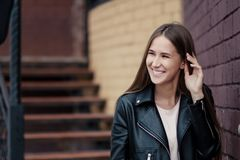 Young beautiful caucasian girl posing in a black leather jacket on a brick wall background. royalty free stock photos