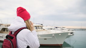 Young beautiful caucasian girl standing on a pier with boats and talks to the mobile phone stock footage