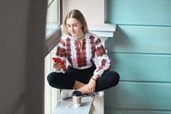 Young beautiful caucasian girl student wearing a vyshyvanka, a traditional Ukrainian embroidered shirt checks her stock image