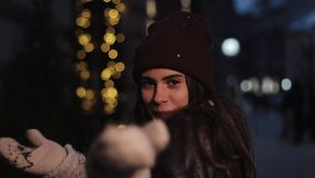 Young beautiful caucasian girl wearing winter clothes, smiling, looking to camera, posing walking at Christmas decorated stock video