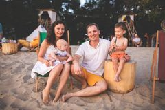 Young beautiful Caucasian happy family of four sitting together embracing at beach cafe in evening sunset. Theme family vacation royalty free stock photography