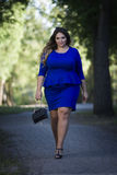 Young beautiful caucasian plus size fashion model in blue dress outdoors, xxl woman on nature royalty free stock image