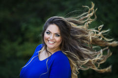 Young beautiful caucasian plus size model in blue dress outdoors, xxl woman on nature with developing in the wind hair Royalty Free Stock Photos