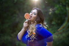Young beautiful caucasian plus size model in blue dress outdoors, xxl woman on nature licking a lollipop Royalty Free Stock Photography