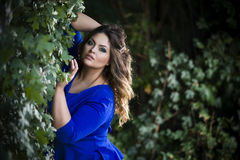 Young beautiful caucasian plus size model in blue dress outdoors, xxl woman on nature Stock Photo