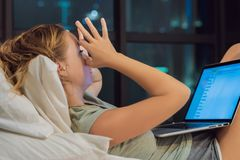 Young beautiful, caucasian, red haired, internet addicted woman working bored, sleepless and tired on her laptop in bed stock photos
