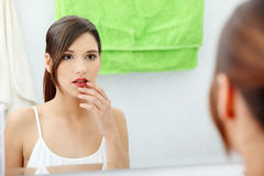 Young beautiful caucasian woman. Stands about a mirror in a bathroom royalty free stock photos