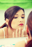 Young beautiful caucasian woman. Stands about a mirror in a bathroom royalty free stock photography